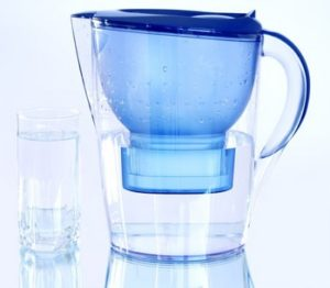 A water filter pitcher sitting next to a glass of clean water.
