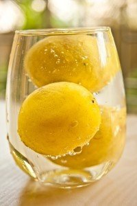 glass of water with whole lemons inside it