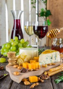 table with a cheese and craker platter with grapes and wine