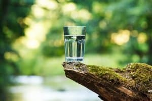 glass of water outside on a rock ledge