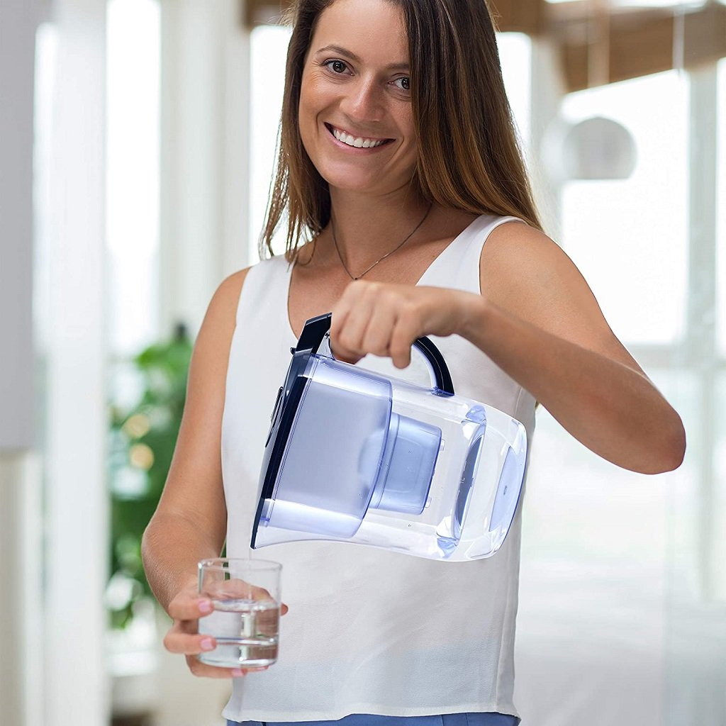 Woman using the EHM alkaline water pitcher in the home